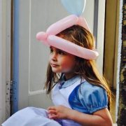 Little girl dressed as Alice In Wonderland wearing a Balloon Hat